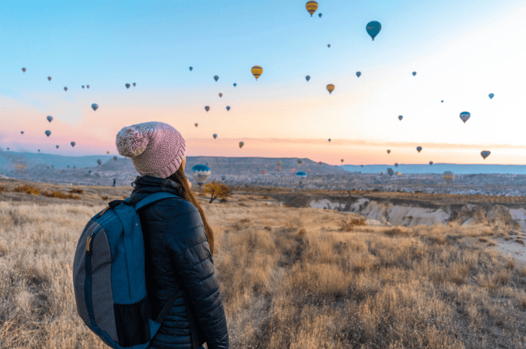 Girl looking at Hot Air Balloon in Sky